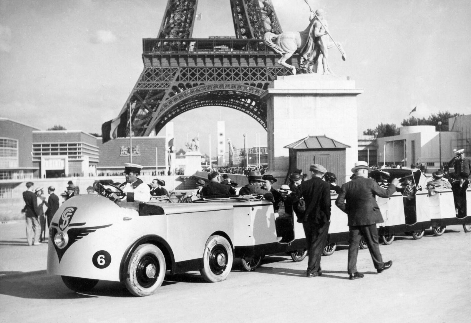 11. 1937. Туристический электропоезд, позволяющий перевозить посетителей  во время Всемирной выставки, проезжает перед Эйфелевой башней