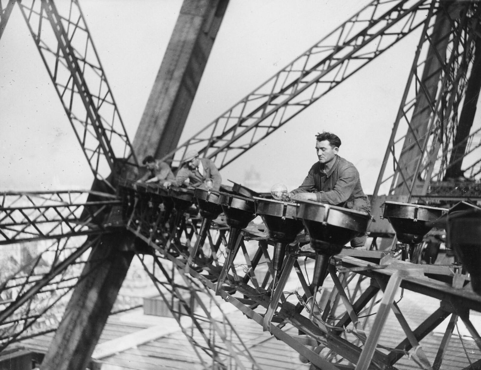 02. 1937. Электрики балансируют на вершине Эйфелевой башне, чтобы установить ночную электрическую подсветку башни