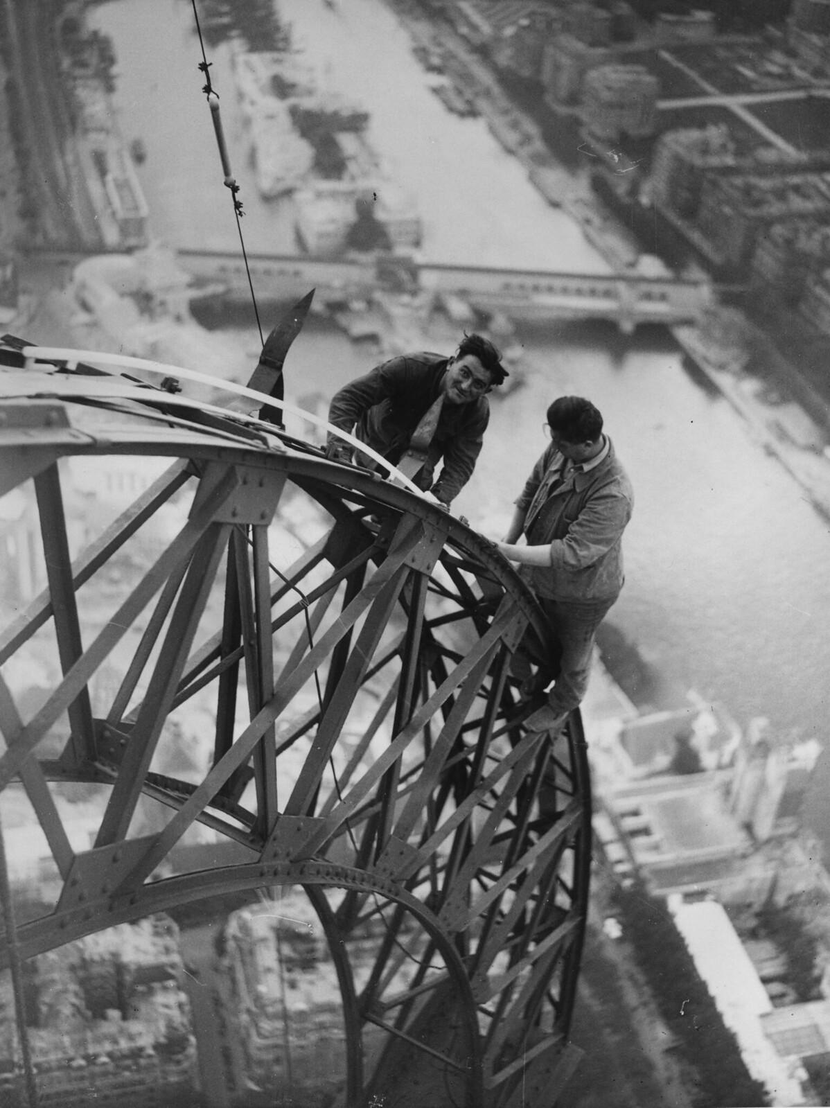 01. 1937. Высоко над рекой Сена два электрика устанавливают электрические гирлянды на Эйфелевой башне, которые будут освещать Всемирную выставку ночью