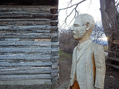 A man carved from wood stands watch on an old cabin at Gellatly Nut Farm Regional Park near Peachland in the BC Okanogan, Canada