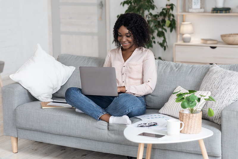 Remote Work. Joyful Black Woman Working On Laptop On Couch At Home