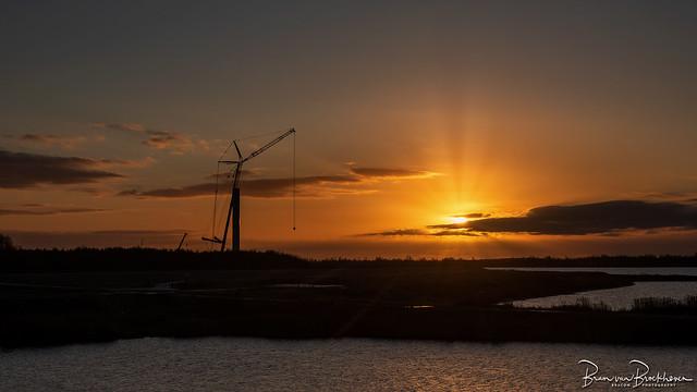 Wind turbine under construction with sunrise