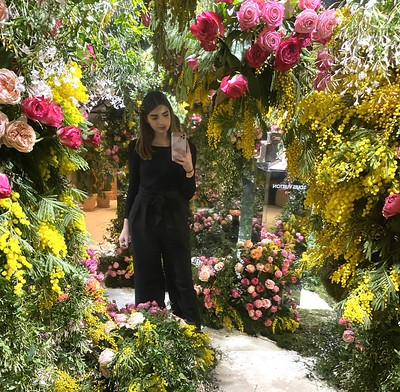 Erasmus+ participant taking a selfie whilst surrounded by flowers