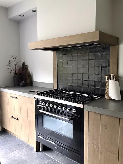 Houten landelijke keuken zwarte tegels achter het fornuis