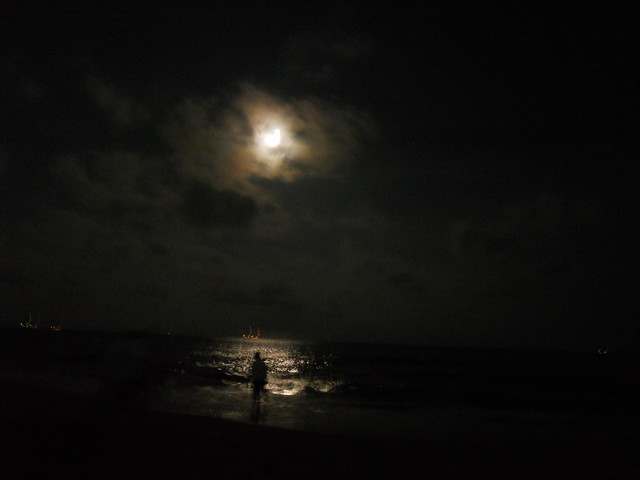 moon and man at night in marina beach, chennai