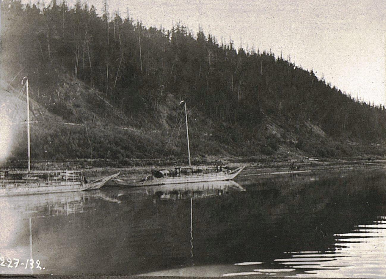 Лодку, идущую против течения, тянут люди и собаки