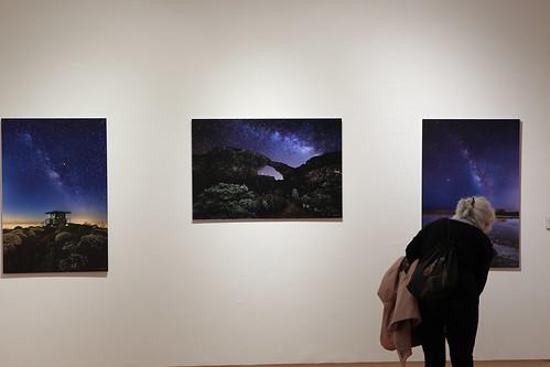 """Una mujer observa una de las fotografías de la muestra """"EstrellArte"""" en la Sala de Arte Agüimes"""