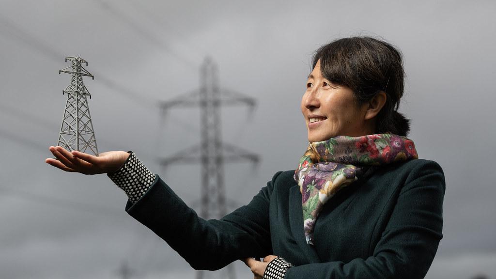 AG的老师站在一个塔前,手里拿着一个小塔模型.