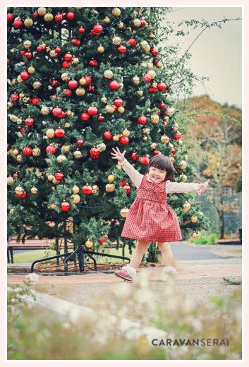 大きなクリスマスツリーの前で踊る女の子