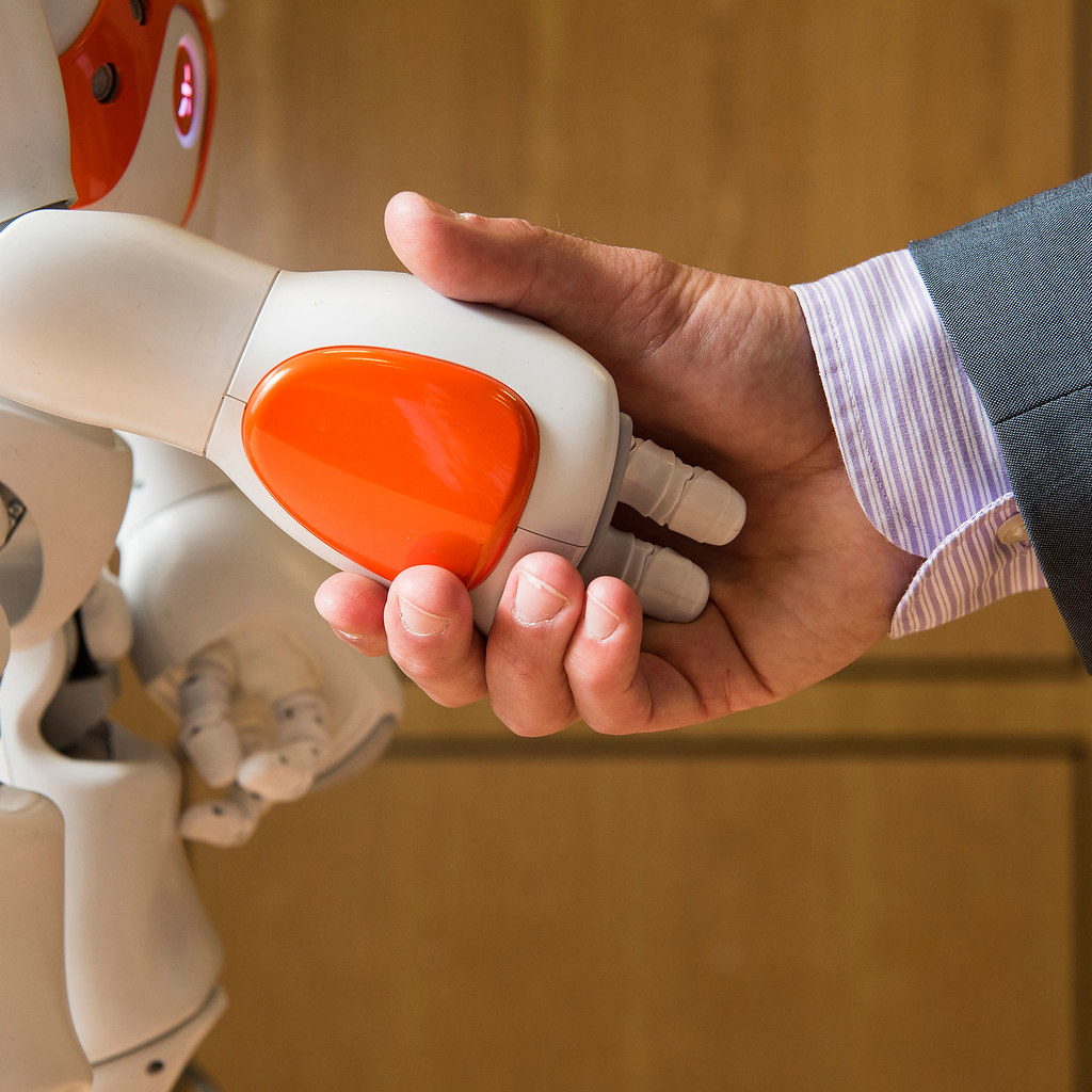 A human hand shaking the hand of a robot
