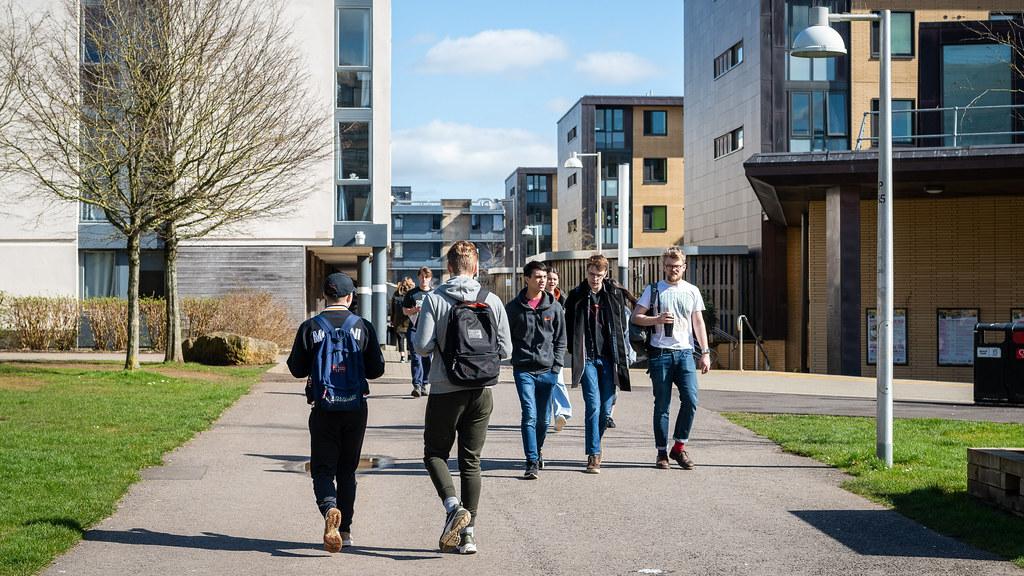 学生们穿过校园里的宿舍楼.