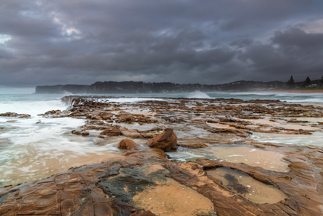 Rock platform, cascades and splashes with rain clouds by the seaside