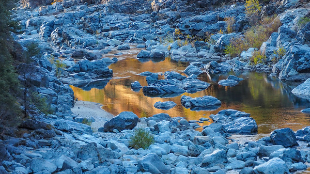 Reflections of sunlit canyon walls amid boulders in shadow, just before sunset, South Yuba River State Park, Nevada County, California