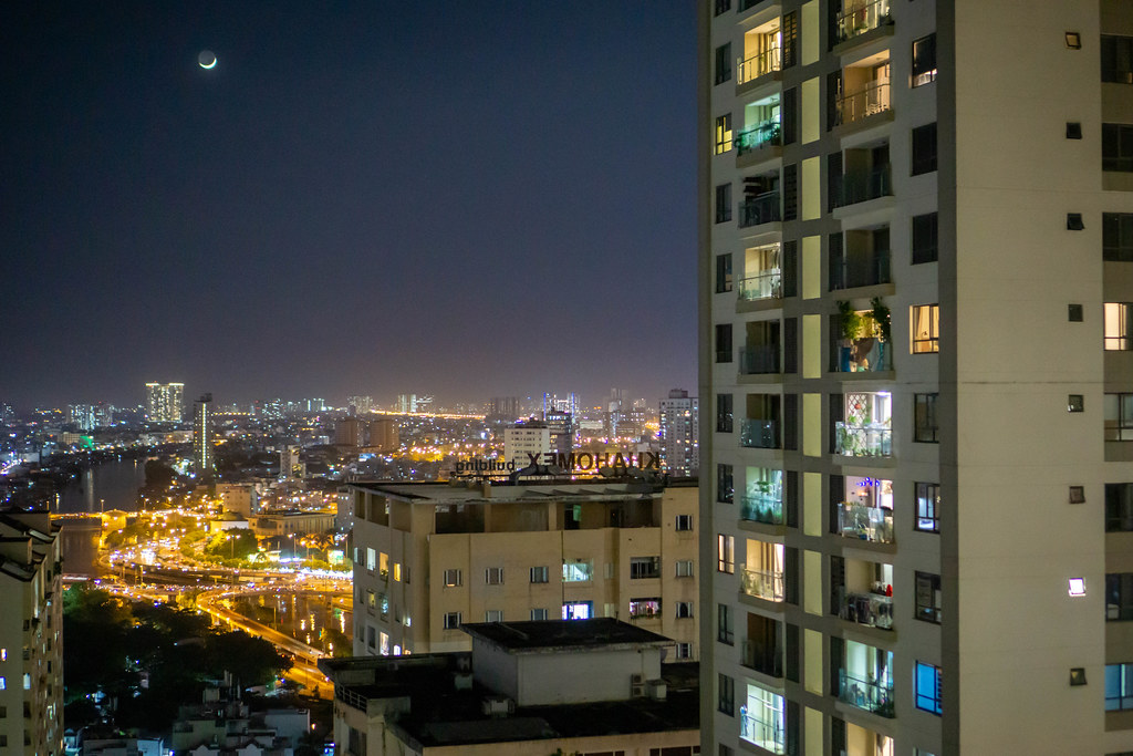 Night Photo of Traffic in Saigon, Saigon River and District 5 with Bright Moon in Ho Chi Minh City, Vietnam