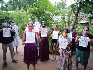 Women members of FTZ & GSEU in Sri Lanka hold signs calling for the ratification of ILO Convention 190 against workplace violence and harassment.
