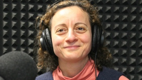 Rana Jawad sits in front of microphone to record podcast