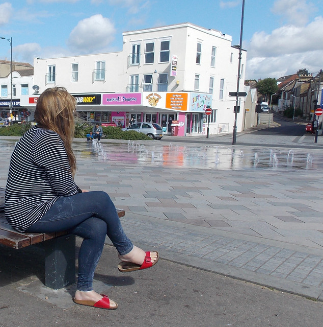 LADY SITTING ON A STREET PUBLIC SEAT IN AT HOLIDAY RESORT ESSEX ENGLAND DSCN1450