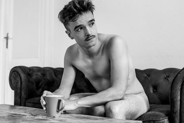 Thomas prend son café sur la canapé.