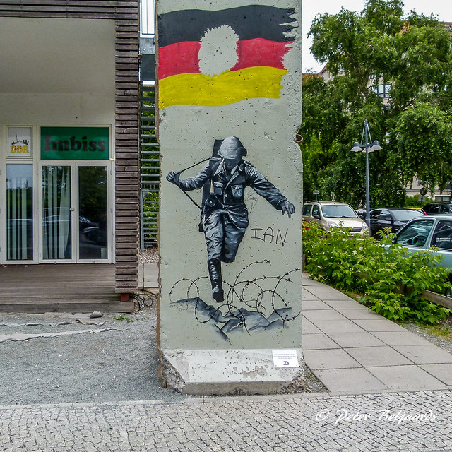 Original piece of the Berlin Wall with an escaping East German soldier, Berlin Germany
