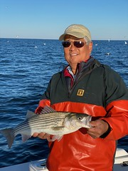 Phot of man holding a keeper-sized striped bass