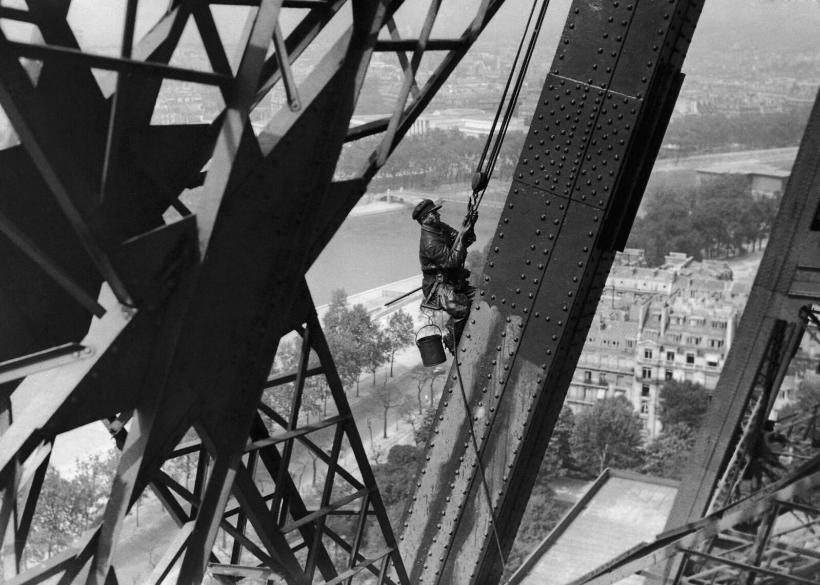 10. 1939Эйфелева башня покрывается свежей краской к своему 50-летнему юбилею. Рабочий висит на высоте 270 метров над землей для выполнения работы 24 мая