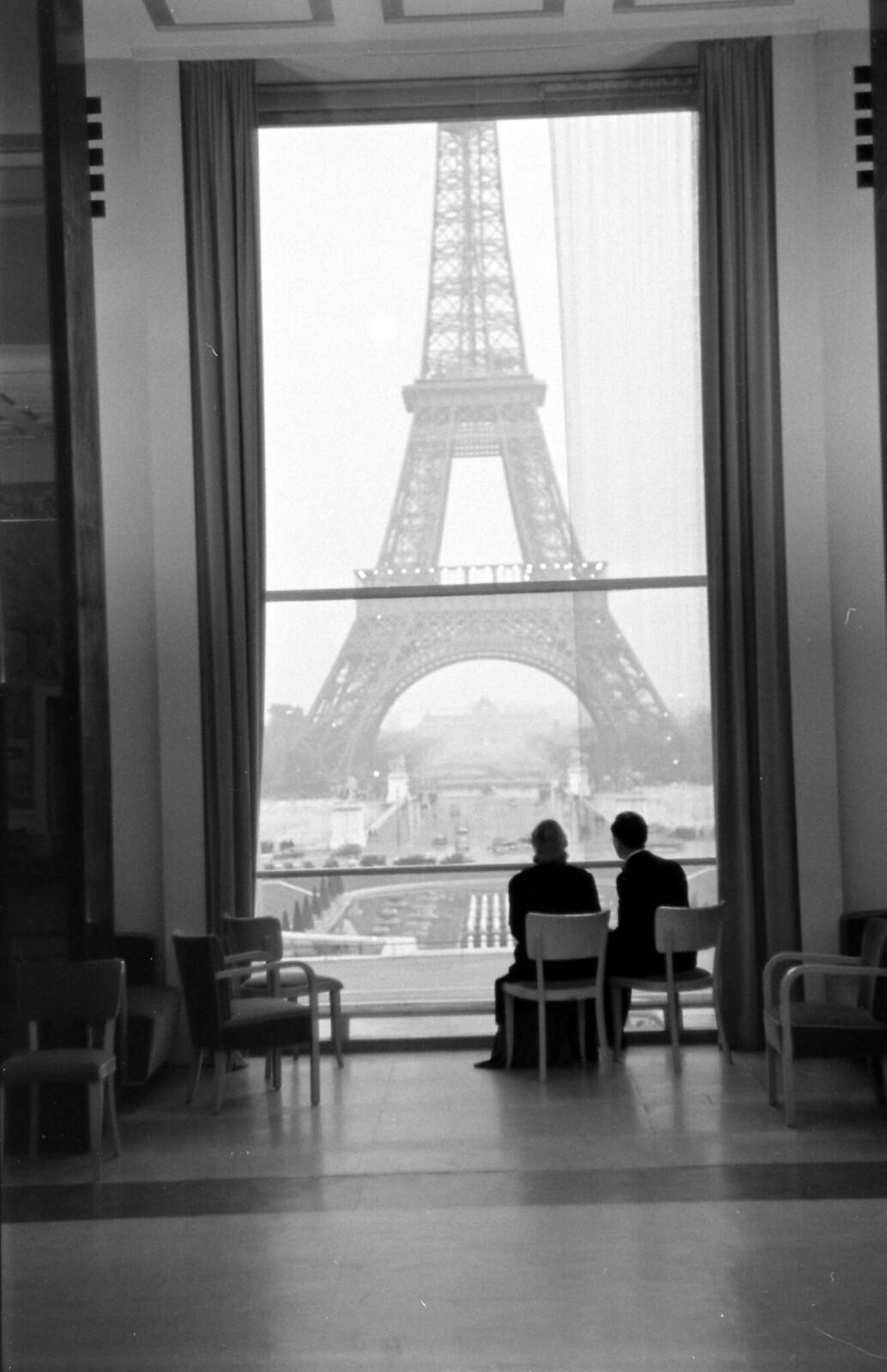 09. 1939. Мужчина и женщина смотрят в окно перед Эйфелевой башней