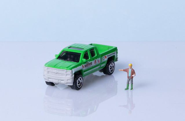 Miniature engineer with hard hat and a green double cab truck