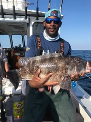 Photo on man on a boat holding a flounder he caught