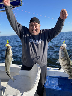 Photo of man on a boat holding two striped bass caught on a tandem line