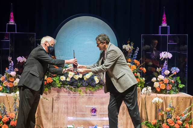 Bruce Gladden receives an award on stage