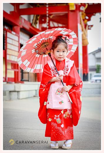 3歳の女の子の七五三 衣装は赤い着物にピンクの被布 赤の和傘