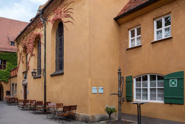 Augsburg, Fuggerei: Markuskirche. In der Ecke zur Sakristei steht ein alter Pumpbrunnen. - St. Mark's Church. In the corner with the sacrsty there is an old pump well