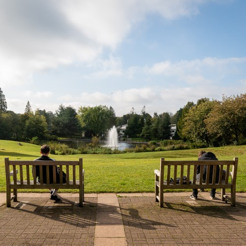 Students sat on benches overlooking the campus lake