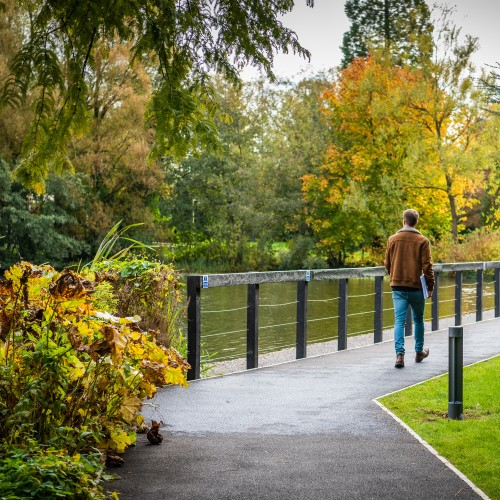 Photo of a person walking alone by the campus lake