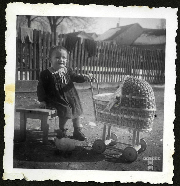 ArchivTappenZAl2a791 Mädchen mit Korbpuppenwagen und Spielzeug, 1930er