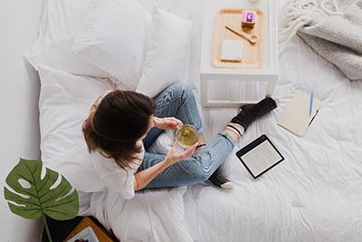 Reading a book on an e-book reader while enjoying a cup of tea.