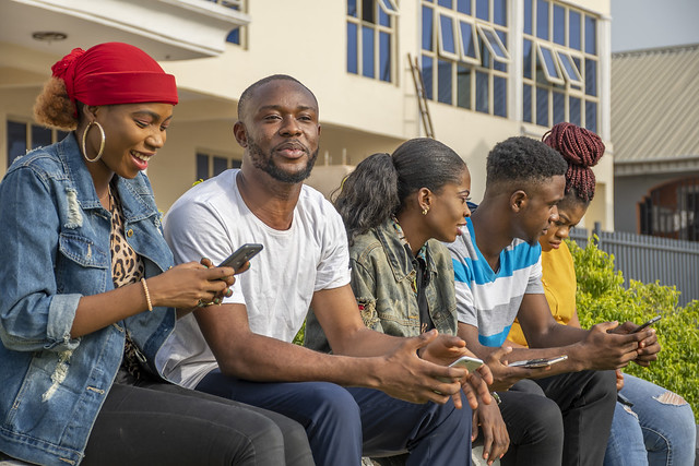group of young africans hanging out together outdoors, having fun, laughing, using their mobile phones