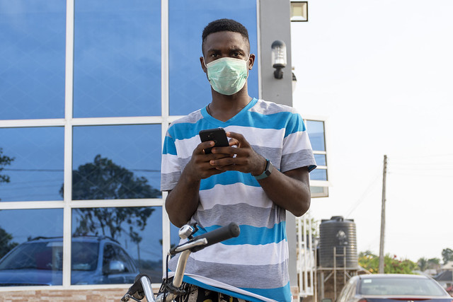 young black man on a bicycle outdoor wearing a face mask to protect against the coronavirus using a mobile phone
