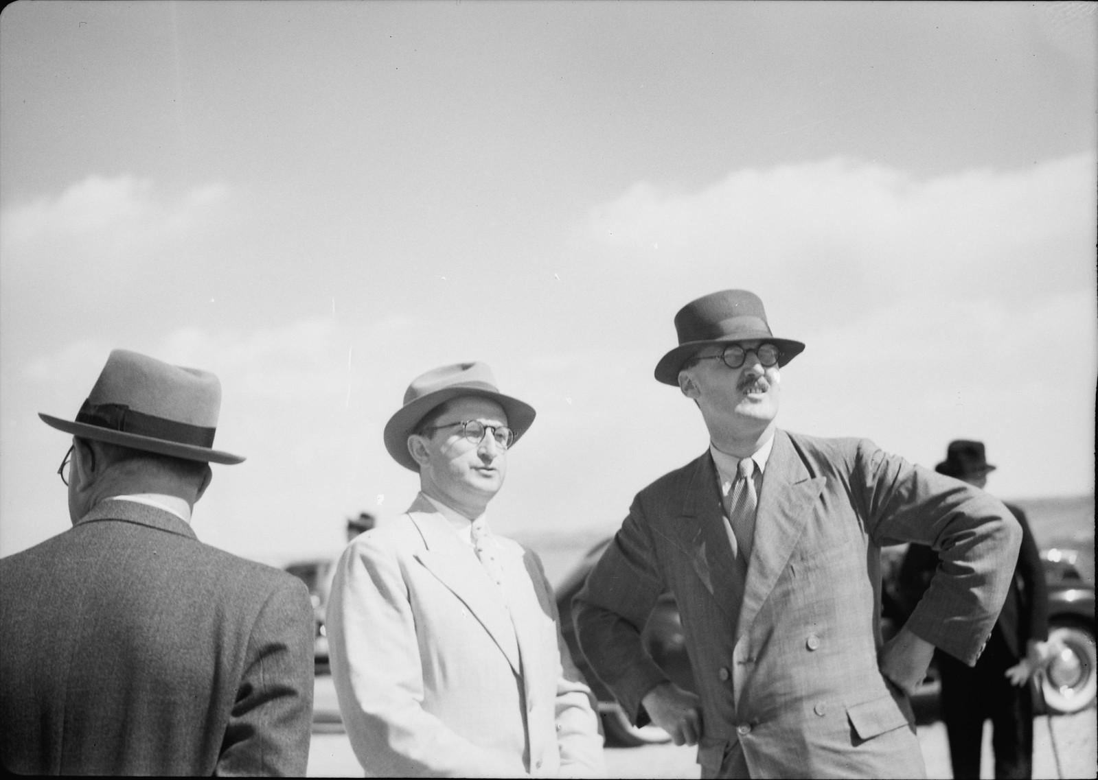 11. Г-н Уильям Денис Баттершил, исполняющий обязанности Верховного комиссара, и г-н Элиаху наблюдают за приближающимся самолетом