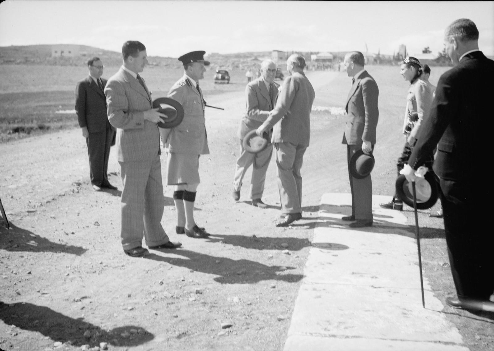 14. Сэр Гарольд МакМайкл пожимает руку майору Гамбли из гражданской авиации и другим правительственным чиновникам.