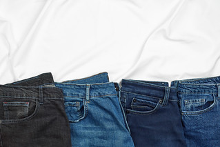 Row of casual jeans pants with copy space | by wuestenigel