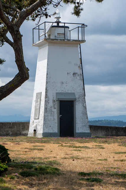 Bush Point Lighthouse, with trees framing the nautical structure on a summer day in Whidbey Island Washington