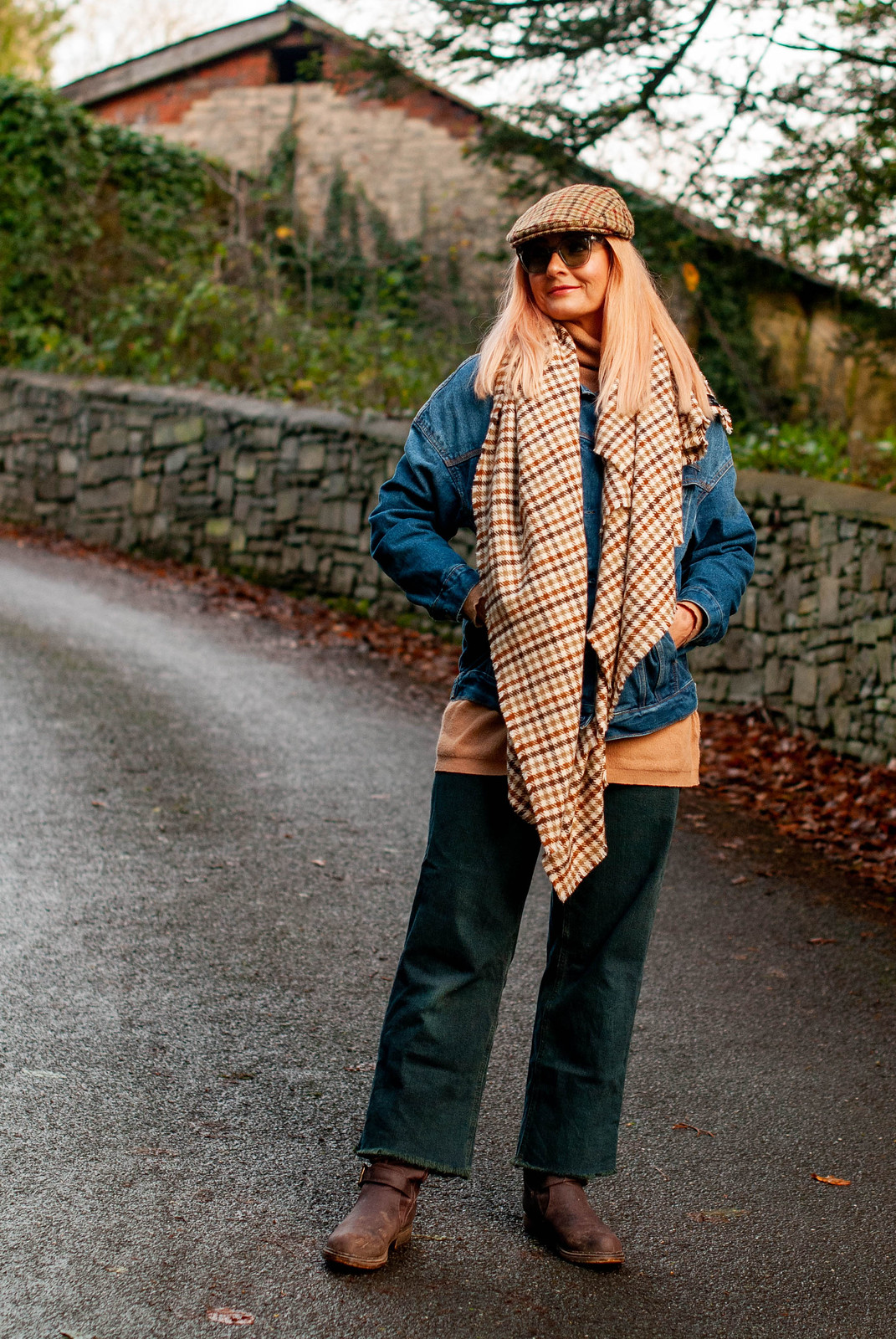 Why It's Perfectly Okay to Wear Unflattering Outfits (Catherine Summers of Not Dressed As Lamb is wearing a tweed flat cap, a woollen tweed scarf, oversized denim jacket, wide leg dark green jeans, camel roll neck sweater and muddy brown boots)