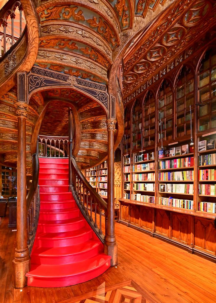 Escalera roja de la librería Lello con una estantería repleta de libros a la derecha