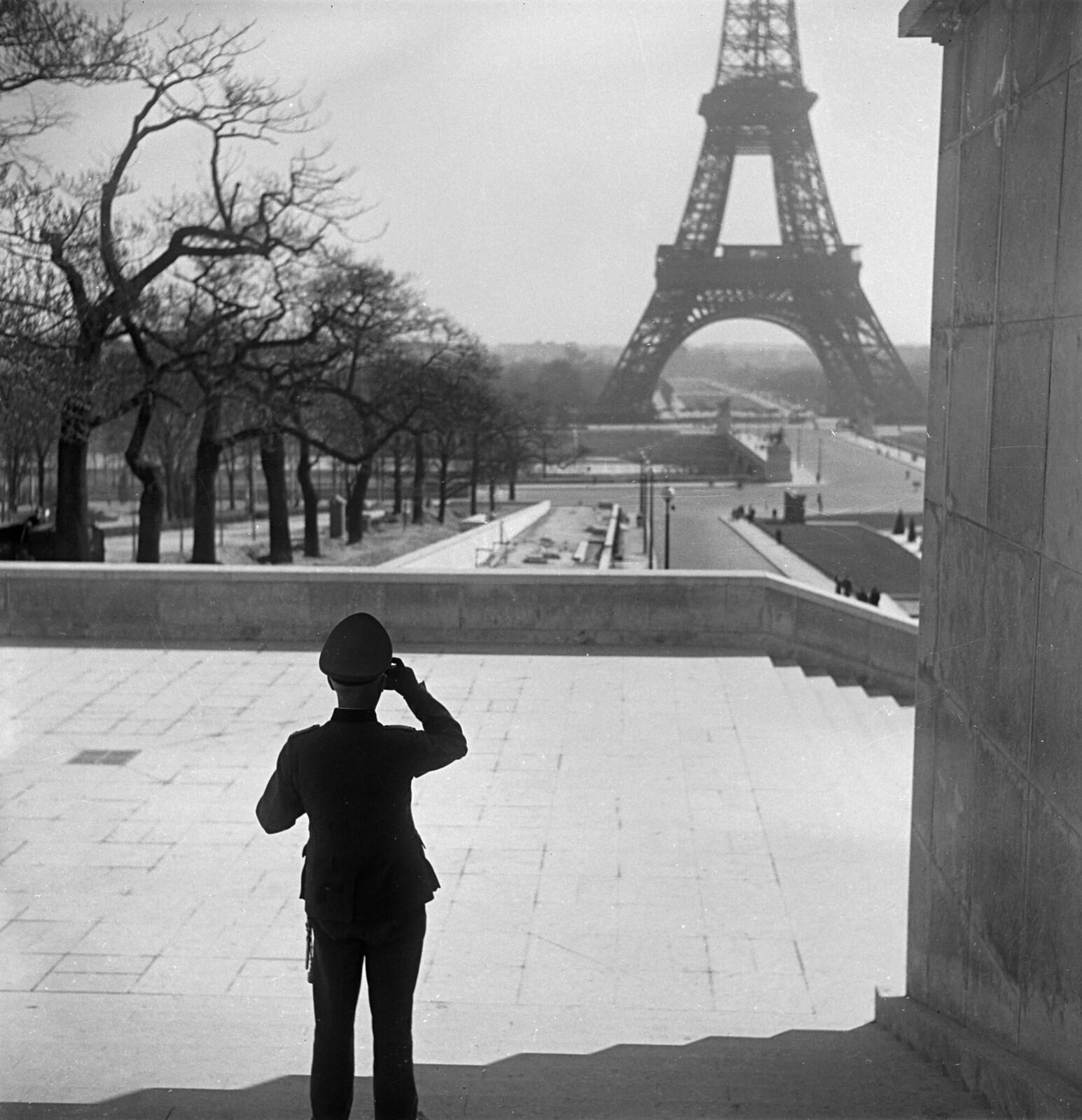 12. Немецкий офицер любуется Эйфелевой башней во дворце Шайо