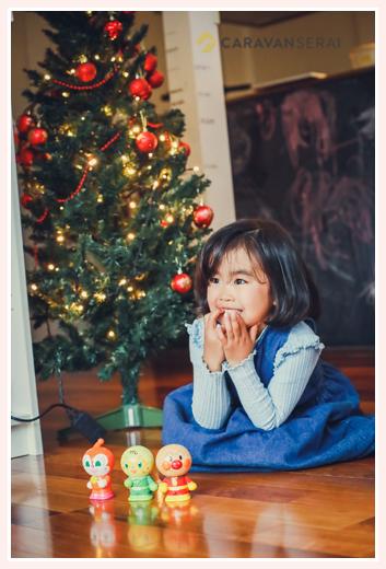 自宅のクリスマスツリーの前で遊ぶ女の子 アンパンマンの人形
