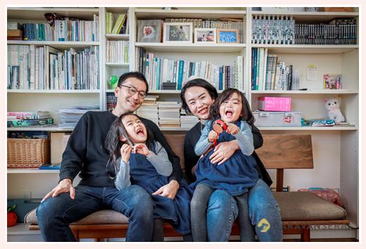 自宅で家族写真 リビングの本棚の前で