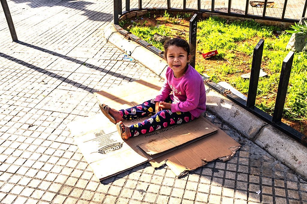 Little girl sitting on cardboard near bus and van terminal on 12-8-20--Beirut