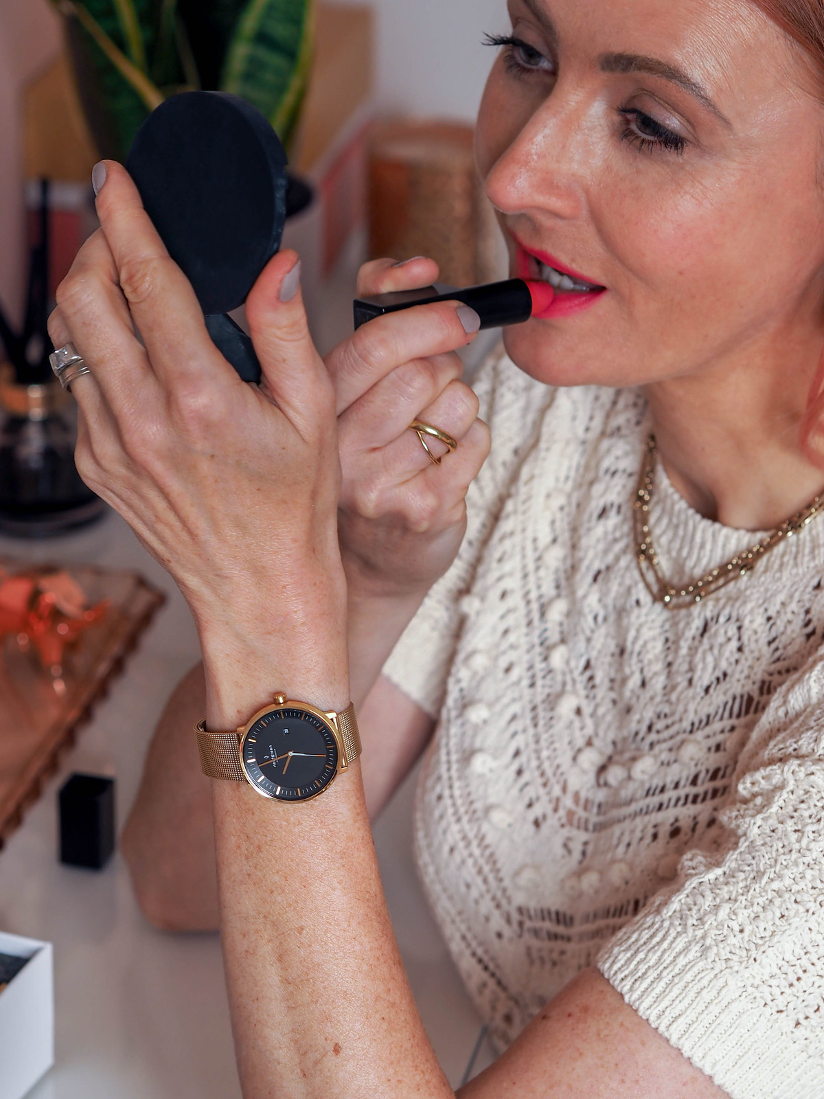 A Classic Black and Gold Watch With Ethical, Sustainable Credentials (Catherine Summers AKA Not Dressed As Lamb is sitting at her dressing table showing off her Nordgreen watch)