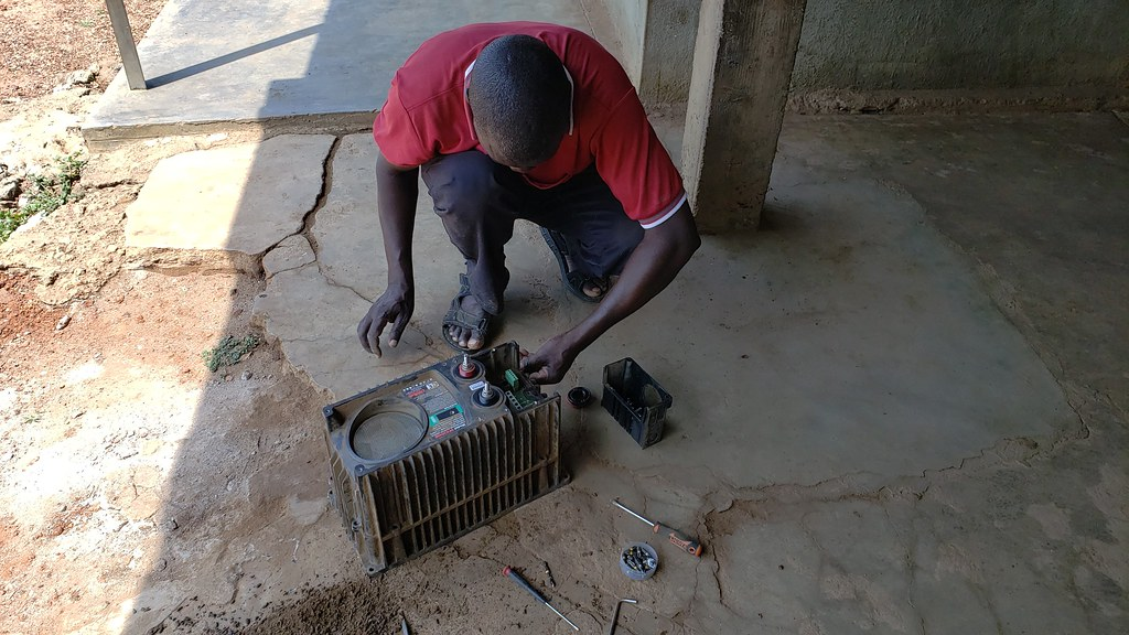 Man bends down and works on inverter.